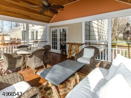 An inviting porch with soaring ceiling & paddle fan