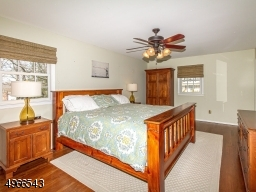Relaxing master bedroom with walk in closet, paddle fan and hardwood floors