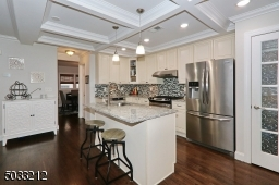 Features incl box beam ceiling, granite counters, tiled backsplash and stainless steel appliances. Kitchen island with gooseneck faucet in sink.