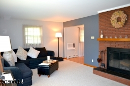 Brick fireplace opening up to dining room room and kitchen