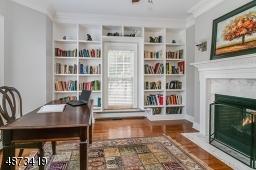 Den/Libarry/Home Office -- tucked into a quiet corner of the 1st floor; gas fireplace, floor-to-ceiling built-ins; door for quiet reading or work.