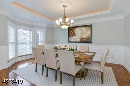 Elegant formal  dining room with tray ceiling; custom millwork, beautiful chandelier included