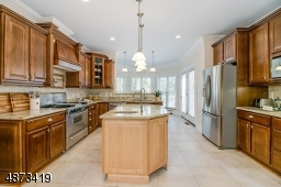 Truly a gourmet kitchen -- ample cabinetry, center island with pendant lighting and prep sink