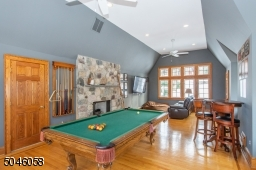 A separate full staircase leads to second floor entertainment area, that features an architectural window, a stone fireplace and vaulted ceilings. A perfect area for a play space, billiard or media room! The possibilities are endless!