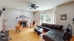 Family Room with Hardwood Floors, a Fireplace and a Bay Window