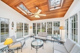 The three season sunroom has windows on 3 sides, a door to the rear yard, and a vaulted ceiling with skylights.