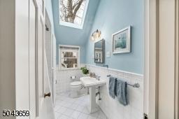 The main hall bath has a tub shower, linen closet and skylight.