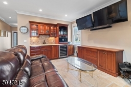 Beverage center with wine refrigerator, sink and built in Miele coffee maker.