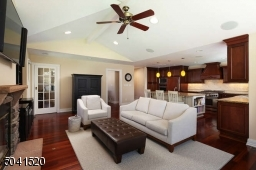Family Room addition with wood burning fireplace, open to the gourmet Kitchen with outside access.
