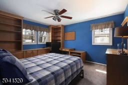 Bedroom with ceiling fan, custom built-ins and closet storage.