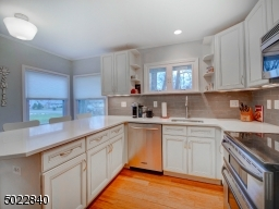 Kitchen with off-white cabinets, stainless appliances, quartz counters