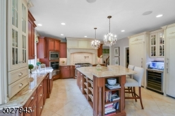 """15' 4"""" X 15' 2 Two-tier center island wit corbels and breakfast seating/additional drawer and cabinet storage/electrical outlet. Imported brazillian Nacarado quartzite Countertops, Schonbek Crystal Chandeliers"""